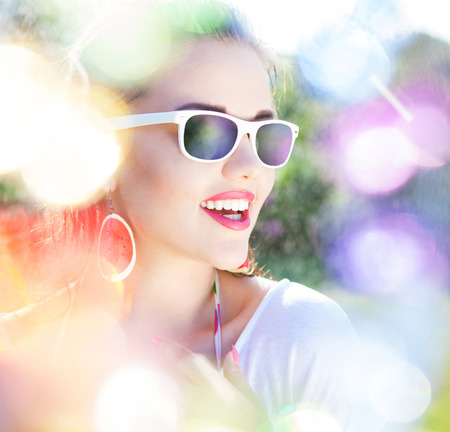 charming: Colorful summer portrait of happy young attractive woman wearing sunglasses and watermelon earrings, beauty and fashion concept natural bokeh and light effect