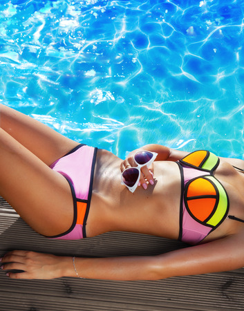 bikini top: Summer holiday fashion and beauty concept - tanning woman wearing neon bikini with sunglasses at the pool on a wooden pier