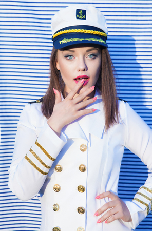 ship captain: Surprised young attractive woman wearing marine captain uniform over stripy background