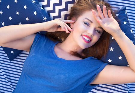 young beautiful woman: Happy beautiful young  woman lying in bed Stock Photo