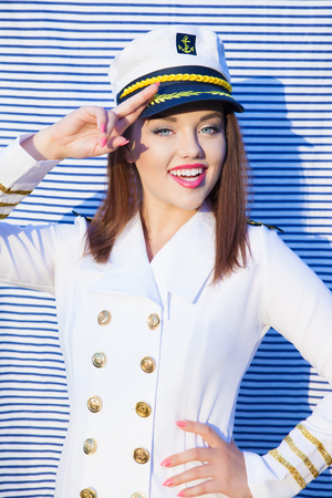 ship captain: Saluting happy young attractive woman wearing marine captain uniform over stripy background