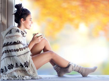 vrouwen: Jonge mooie brunette vrouw met een kopje koffie dragen gebreide nordic druk poncho zit thuis bij het raam. Wazig tuin vallen achtergrond.