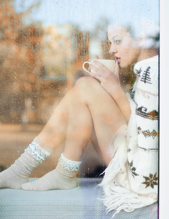 sock: Beautiful thoughtful brunette woman with cup of coffee wearing knitted nordic print poncho sitting home by the window.. Blurred garden fall background.
