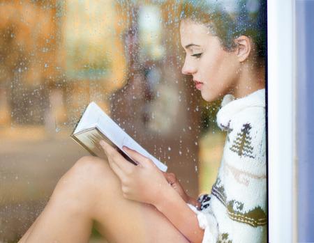 frio: Hermoso libro de lectura joven mujer morena llevaba vestido sentado en casa detrás de una ventana cubierta de gotas de lluvia de punto. Borrosa jardín de otoño reflexión sobre el vidrio. Lloviendo concepto otoño