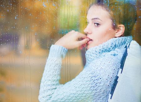 Nadenkende mooie jonge donkerbruine vrouwenzitting achter een venster dat met regendalingen wordt behandeld. Wazig herfst tuin reflectie op het glas. Stockfoto