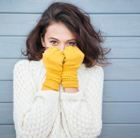 moda: Mulher jovem natural bonita morena, sorrindo, vestindo suéter e luvas de malha. Outono e inverno moda conceito.