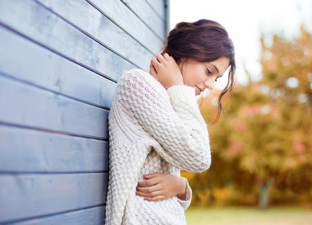 Mooie natuurlijke jonge brunette vrouw draagt gebreide trui van het huis. Herfst en winter mode-concept.