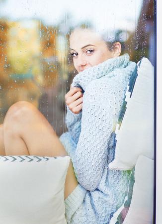 Mooie jonge brunette vrouw dragen gebreide jurk thuis te zitten achter een raam bedekt met regendruppels. Vage val tuin reflectie op het glas.
