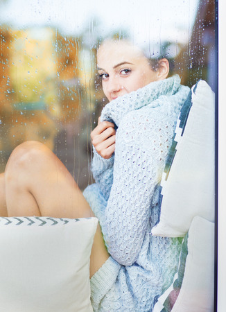 Beautiful young smiling brunette woman wearing knitted dress sitting home behind a window covered with rain drops. Blurred fall garden reflection on the glass.