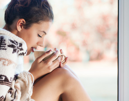Jonge mooie brunette vrouw met een kopje koffie dragen gebreide nordic druk poncho zit thuis bij het raam. Wazig tuin vallen achtergrond.