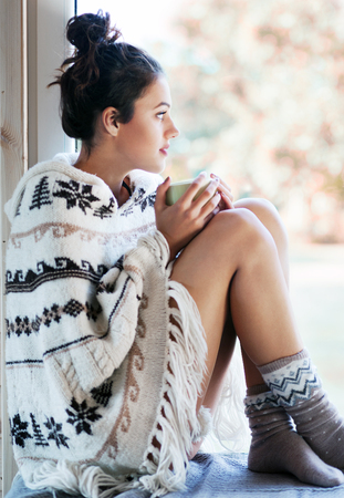 Beautiful thoughful  brunette woman with cup of coffee wearing knitted nordic print poncho sitting home by the window.. Blurred  garden fall background.
