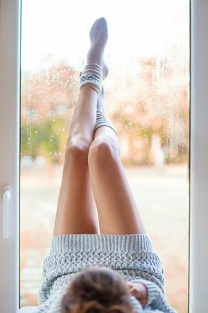 노르딕 프린트 양말과 창에 의해 집에서 누워 니트 드레스를 입고 아름다운 다리를 가진 젊은 여자. 흐린 정원 가을 배경.