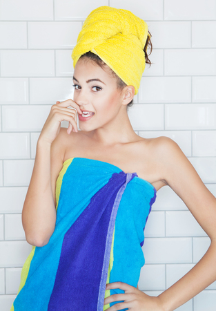 towel: Beautiful young brunette woman in the bathroom, covered with towels, white tiles in the background