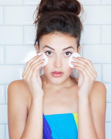 Make-up verwijdering concept, jonge aantrekkelijke vrouw bedekt met handdoek met katoenen pads Stockfoto