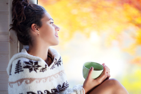 Young Beaufort brunette smiling woman with cup of coffee wearing knitted nordic print poncho sitting home by the window. Blurred garden fall background.