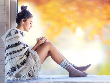 커피 한잔과 젊은 아름 다운 갈색 머리 웃는 여자는 창에 의해 집에 앉아 노르딕 프린트 판초 니트 입고. 흐린 정원 가을 배경입니다.