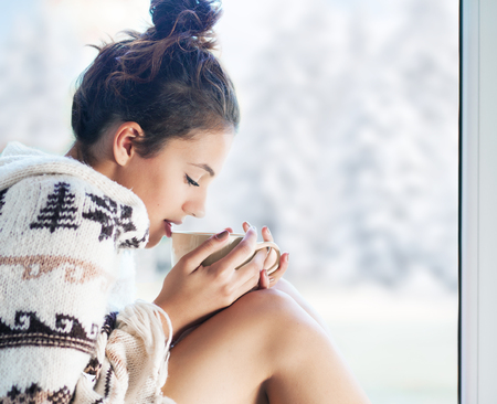 Young beautiful brunette woman drinking cup of coffee wearing knitted nordic print poncho sitting home by the window. Blurred winter snow tree background. Stock Photo