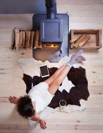 Young woman with cup of coffee sitting home on a cow rug by the fireplace. Fall winter relaxing and leisure concept. Stok Fotoğraf