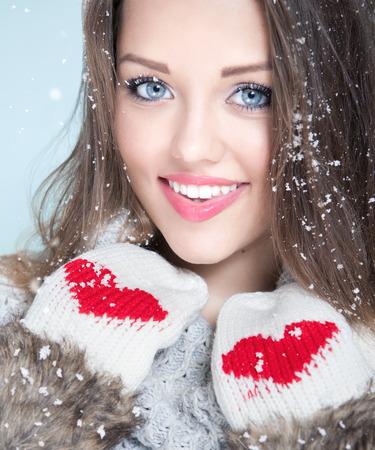 Mooie gelukkige lachende jonge vrouw met winterhandschoenen bedekt met sneeuwvlokken. Kerstportretconcept.