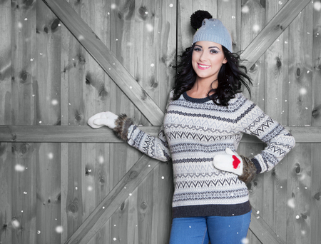woman clothes: Beautiful young happy smiling woman wearing winter hat and gloves covered with snow flakes. Christmas portrait concept Stock Photo