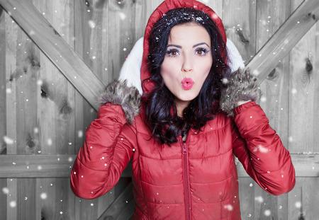 neige noel: Belle jeune femme portant surpris hiver veste à capuche et des gants recouverts de flocons de neige. Notion de portrait de Noël. Banque d'images