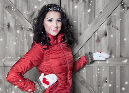 fashion girl: Beautiful young happy smiling woman wearing winter jacket and gloves covered with snow flakes. Christmas portrait concept.