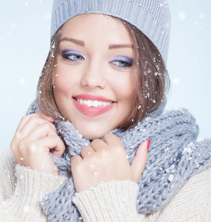 Winter face close up of young attractive happy smiling woman covered with snow flakes. Christmas concept.