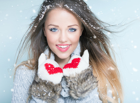 beautiful face woman: Face close up of beautiful happy young woman wearing winter gloves covered with snow flakes. Christmas snowing portrait concept.