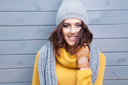 winter weather: Beautiful natural young smiling brunette woman wearing knitted sweater, leather gloves, scarf and hat. Covered with snow flakes. Fall and winter fashion concept.