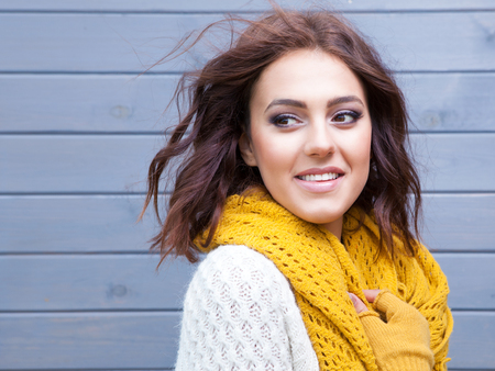 woman smiling: Beautiful natural young smiling brunette woman wearing knitted sweater gloves and scarf. Fall and winter fashion concept.