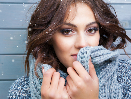 natural face: Beautiful natural looking young smiling brunette woman, wearing knitted scarf, covered with snow flakes. Snowing winter beauty concept