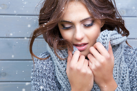 Beautiful natural young brunette woman with eyes closed, wearing knitted scarf, covered with snow flakes. Snowing winter beauty concept. Banco de Imagens