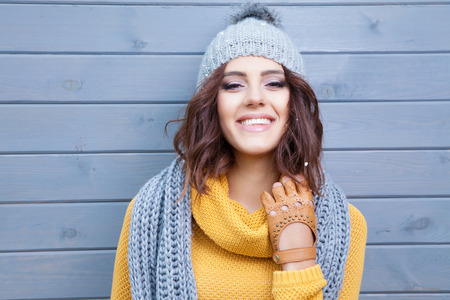 scarf: Beautiful natural young smiling brunette woman wearing knitted sweater, leather gloves, scarf and hat. Covered with snow flakes. Fall and winter fashion concept.
