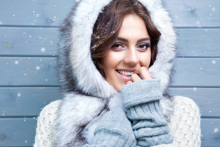 Beautiful young smiling brunette woman wearing knitted sweater and fur hood, covered with snow flakes. Snowing winter beauty concept. Stok Fotoğraf