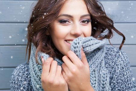 skönhet: Naturskön ung leende brunett kvinna, klädd i stickad halsduk, täckt med snöflingor. Det snöar vinter skönhet koncept.