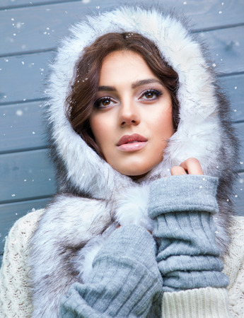 fur hood: Beautiful young pensive brunette woman wearing knitted sweater and fur hood, covered with snow flakes. Snowing winter beauty concept. Stock Photo