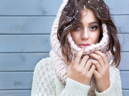 winter fashion: Winter portrait of young beautiful brunette woman wearing knitted snood covered in snow. Snowing winter beauty fashion concept. Stock Photo