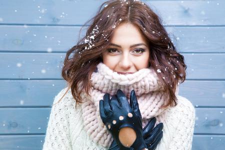 身に着けている若い美しいブルネットの女性の冬の肖像ニット スヌードが雪で覆われています。雪が降る冬美容ファッションのコンセプトです。