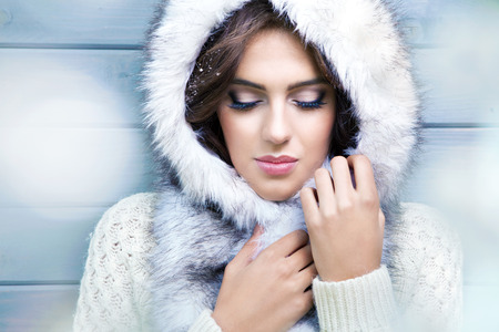 fur hood: Beautiful young brunette woman with eyes closed, wearing knitted sweater and fur hood, covered with snow flakes. Snowing winter beauty concept.