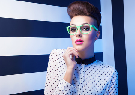 Beleza: jovens Vidros desgastando Mulher surpreendida atrativas no stripy fundo, beleza e conceito de moda