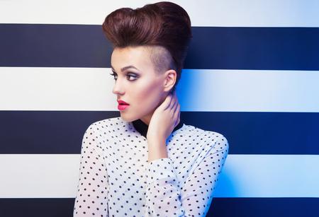 bollos: Atractiva camisa de mujer elegante joven con lunares en el fondo de rayas, la belleza y el concepto de moda