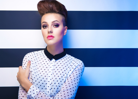 Attractive young elegant woman wearing polka dot shirt on stripy background, beauty and fashion concept