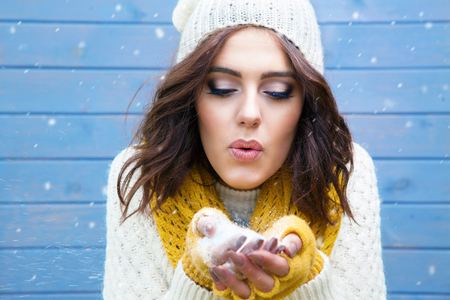 Winter portrait of young beautiful brunette woman wearing knitted hat blowing snow. Snowfall winter beauty fashion concept.
