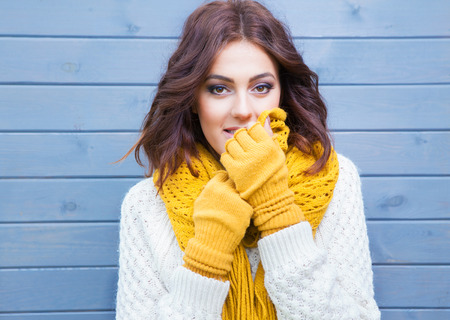 yellow fleece: Beautiful natural young smiling brunette woman wearing knitted sweater and gloves. Fall and winter fashion concept. Stock Photo