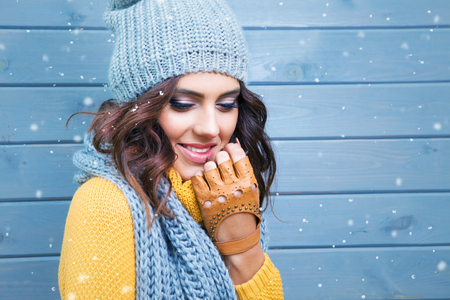 winter fashion: Beautiful natural young smiling brunette woman wearing knitted sweater, leather gloves, scarf and hat. Covered with snow flakes. Fall and winter fashion concept.