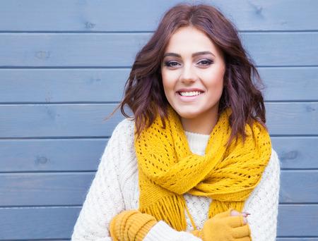 아름 다운 자연 젊은 웃는 갈색 머리 여자 입고 니트 스웨터 장갑 및 스카프. 가 및 겨울 패션 개념입니다.