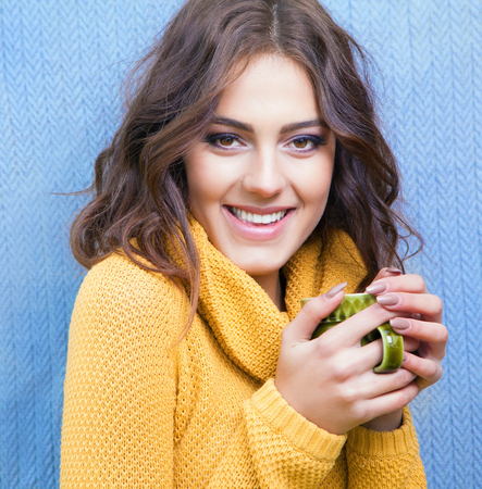 Beautiful natural young smiling brunette woman wearing knitted sweater drinking cup of coffee Standard-Bild