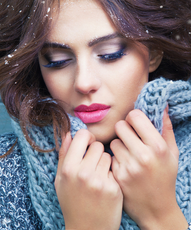 Beautiful natural young brunette woman with eyes closed, wearing knitted scarf, covered with snow flakes. Snowing winter beauty concept. Standard-Bild