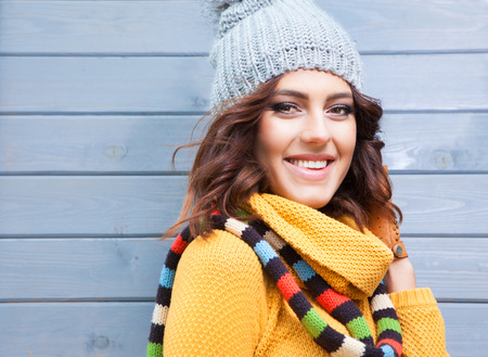 Beautiful natural young smiling brunette woman wearing knitted sweater, leather gloves, scarf and hat. Fall and winter fashion concept.