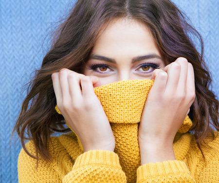 웃는 눈을 가진 아름 다운 자연 젊은 수줍은 갈색 머리 여자 스웨터 니트 입고